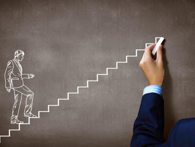 Man draws a businessman walking up stairs on chalkboard