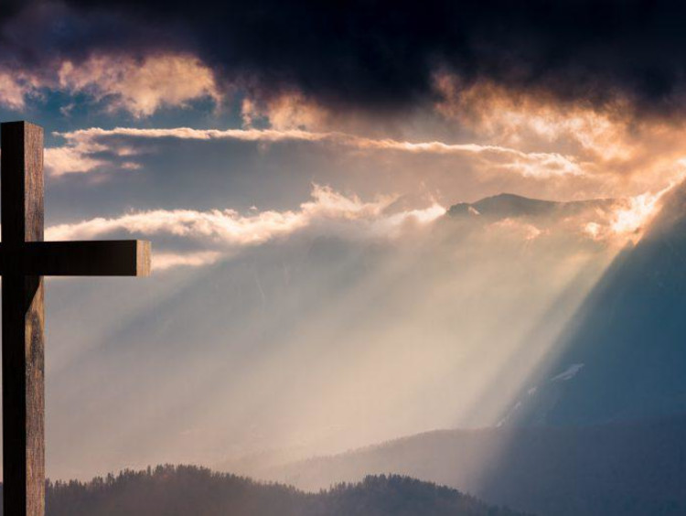A cross facing golden sun-rays