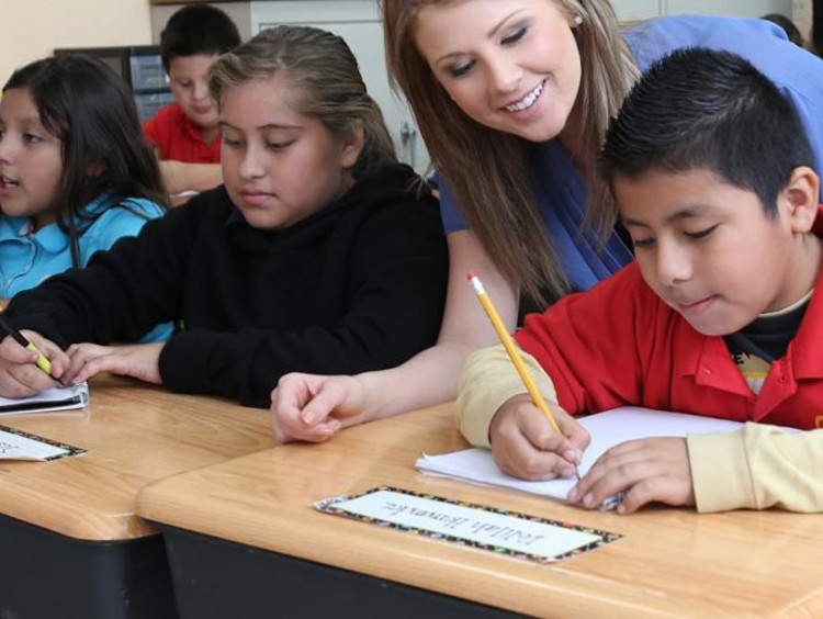 teacher helping her students in class
