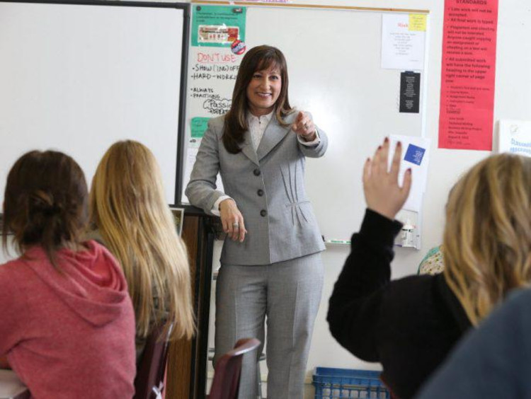 Adult woman instructs in a classroom setting.