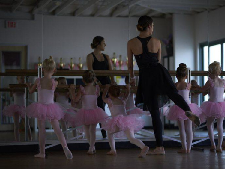 Ballet teacher leads little girls barre movements