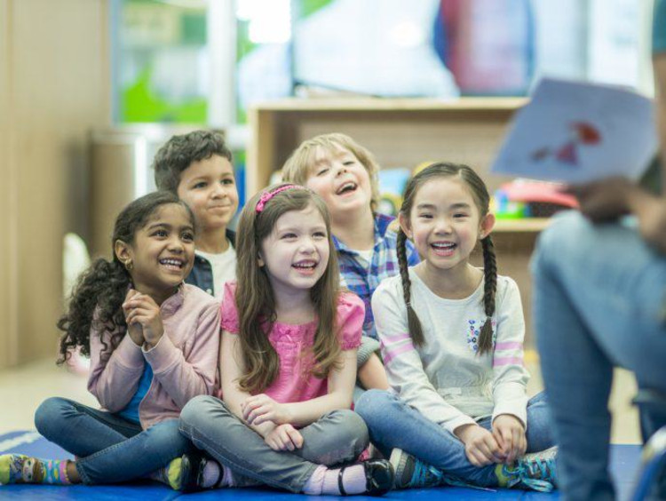 Group of kids laugh sitting on the ground during story time
