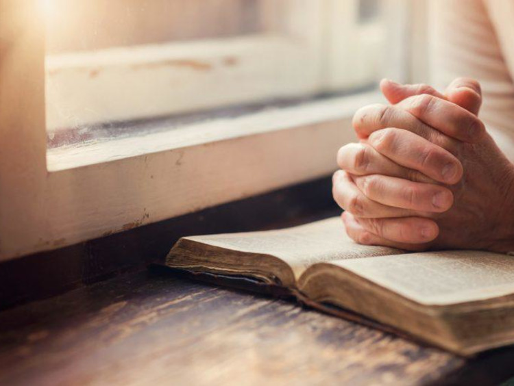 man with folded hands praying on a bible