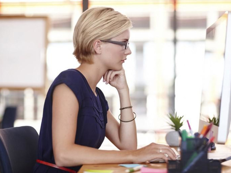 Professional woman with short hair uses a Mac desktop in office space