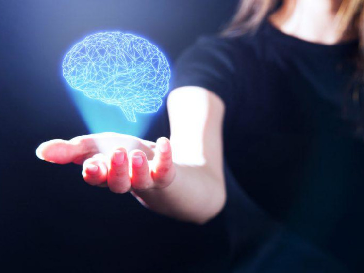 Woman holds her hand out with a virtual brain above it
