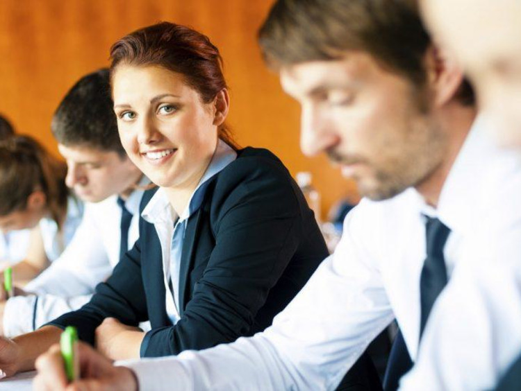 Group of professionals take assessment and girl turns head to smile