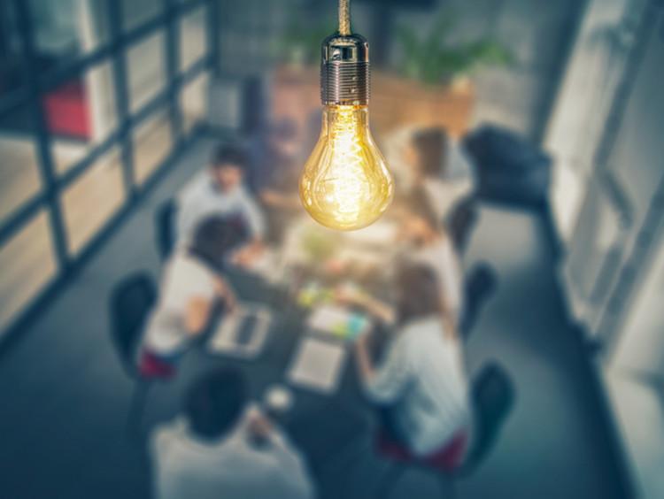 light bulb over team of people