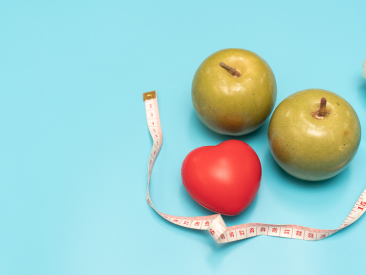 two apples with a heart and measuring tape