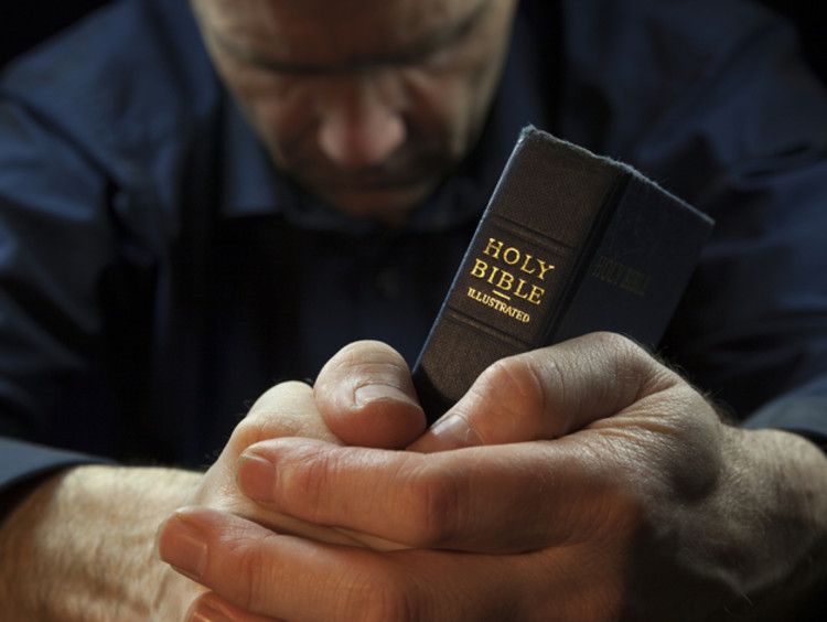 a man holding the bible between his hands and praying