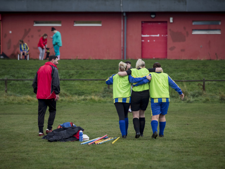 Athletic trainer helping injured student on soccer field