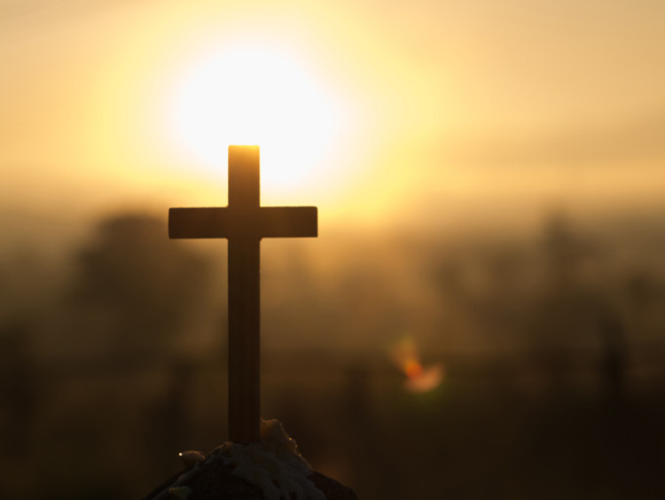 cross being held up to the sun by someone