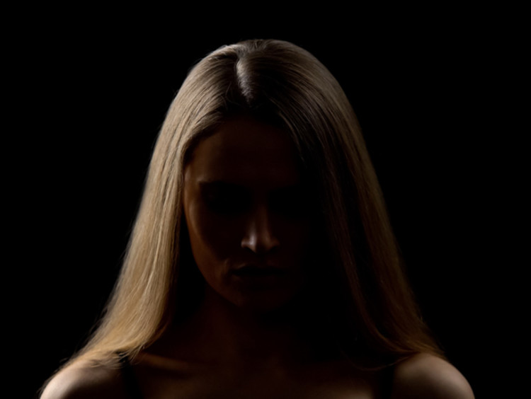 person standing in a dark area with light on one side of their face