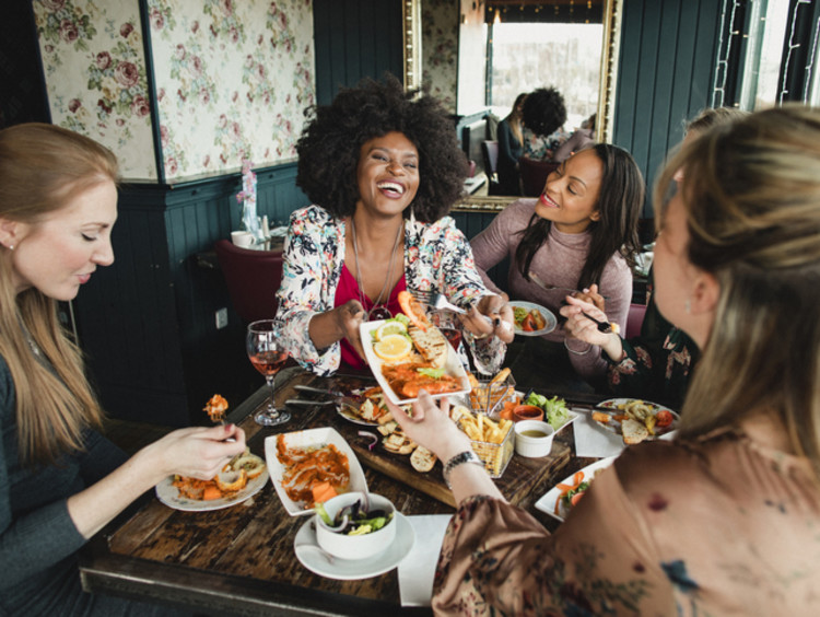 girls laughing and eating brunch
