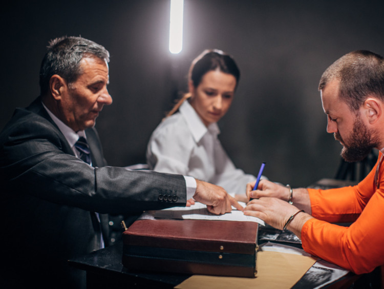 Probation officer shaking hands with convict at desk with paperwork