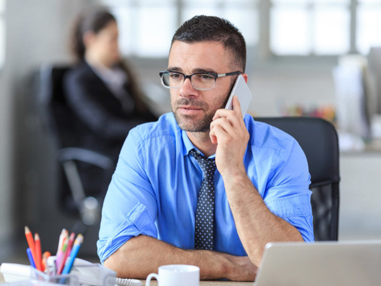 man with glasses speaking on phone in office