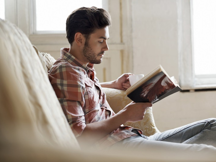 Man reading with a drink on a couch