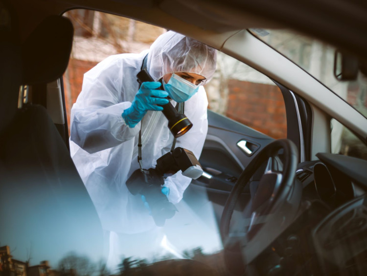 A forensic scientist takes pictures at a crime scene