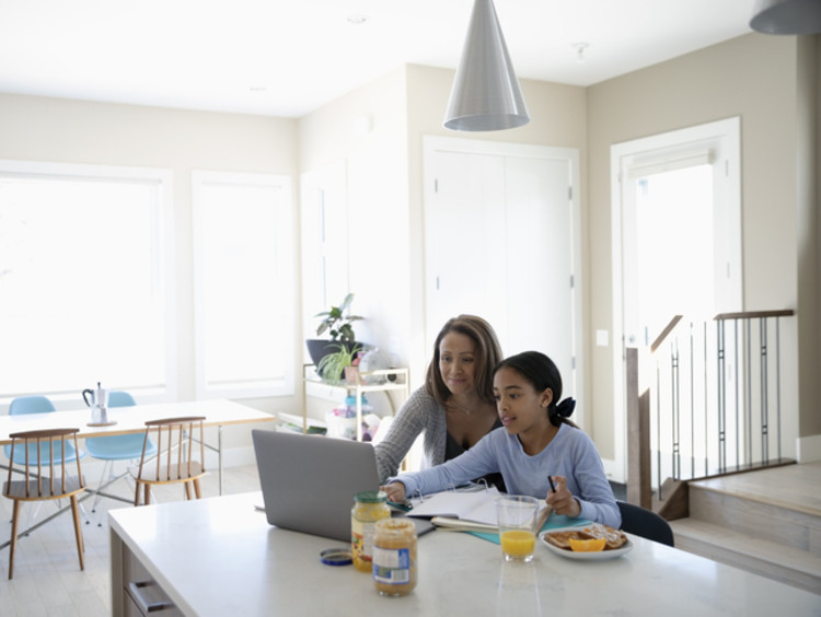 An elementary student doing blended classwork at home with her mother