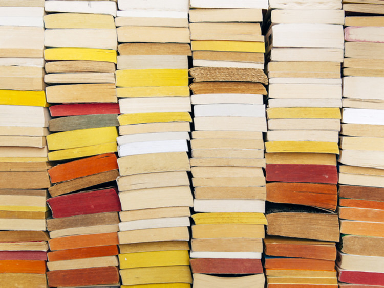 A stack of books in warm colors against a wall