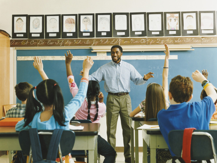 A classroom full of students raising their hands to answer a question