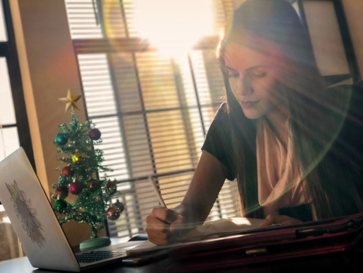 A girl working on homework by a Christmas tree