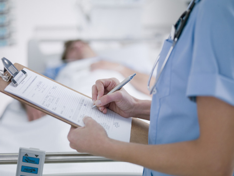 RN with nursing degree filling out paperwork beside patient
