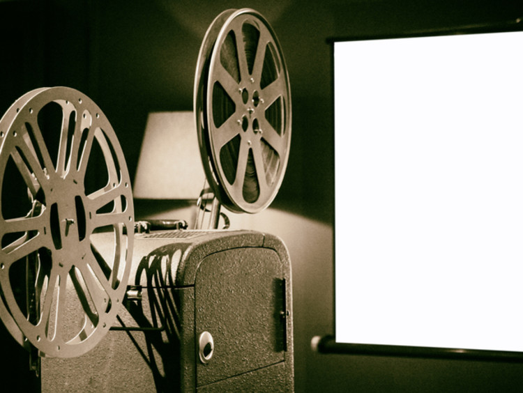 An old film projector projecting onto a screen