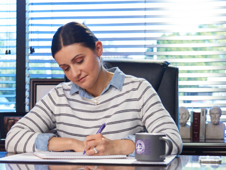 woman admin leader works at desk in office setting