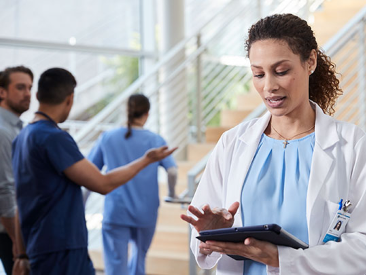 Woman medical admin uses an ipad in clinical setting