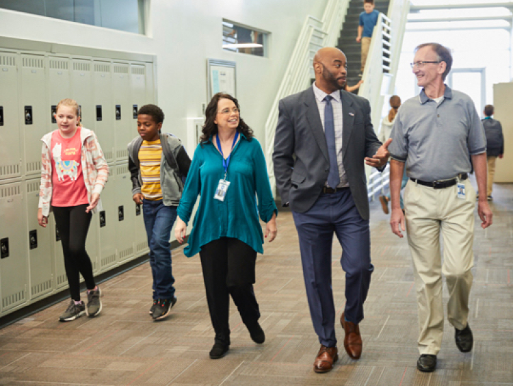 faculty, educational leaders and students walk and talk in a school hallway