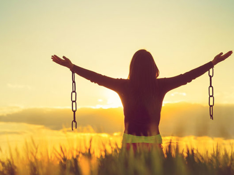 girl in field holding arms out with broken chains