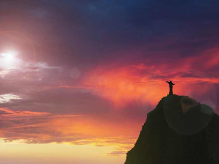 Person stands with arms stretch looking into Godly sky at sunset