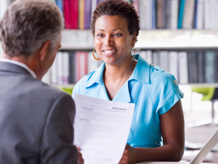 A teaching candidate handing her curriculum vitae to an interviewer