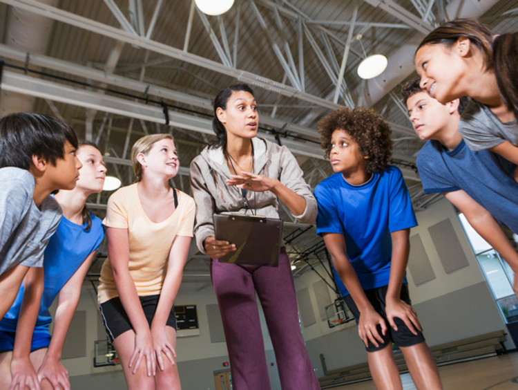 A PE teacher in a huddle with a group of her students