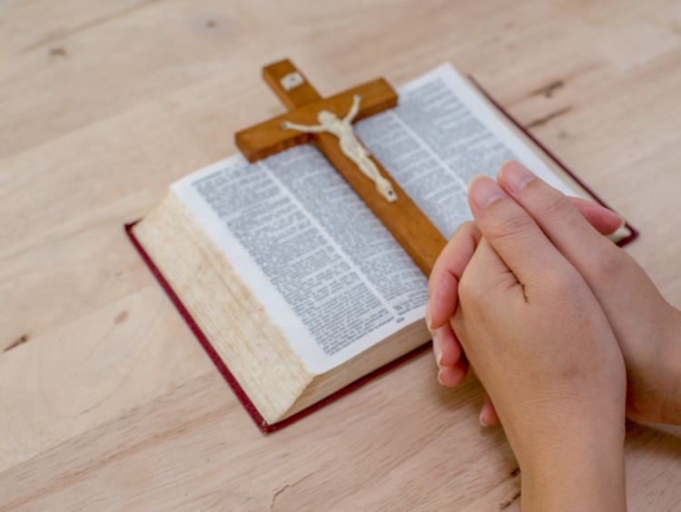 Praying hands are accompanied by a cross and Bible