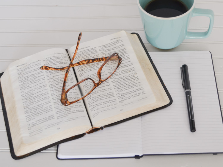 Bible surrounded by notebook, coffee and glasses