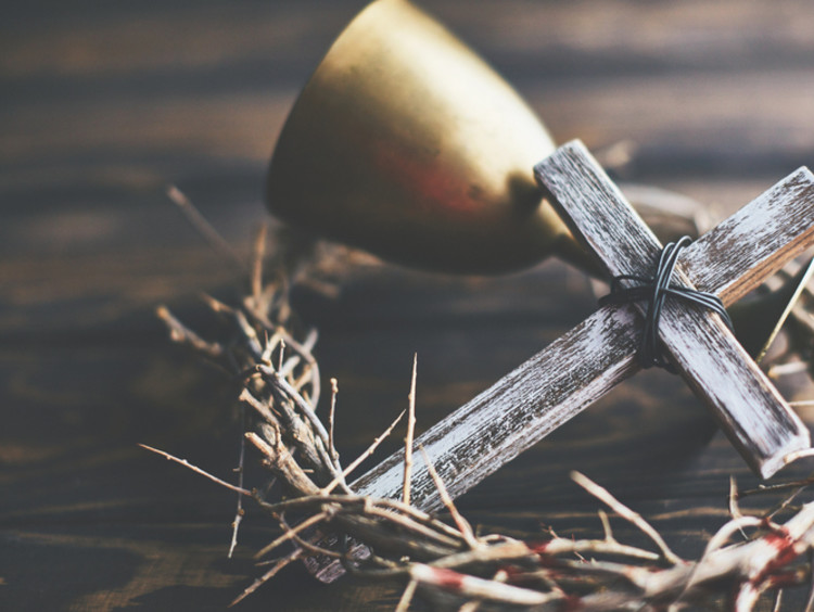 A cross lays with a crown of thorns and chalice