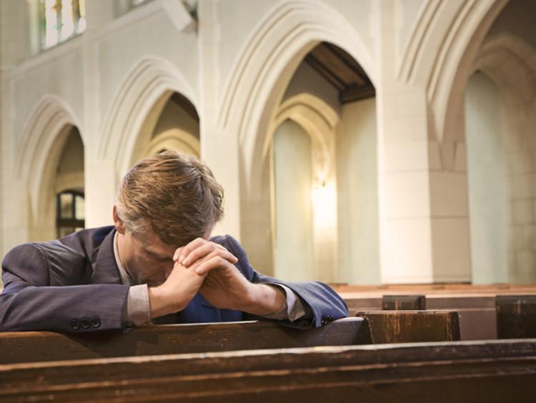 Man bows his head to pray in church for forgiveness