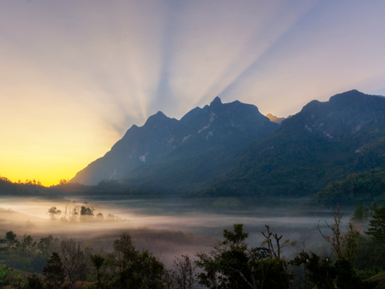 The sun rises behind a mountain backdrop