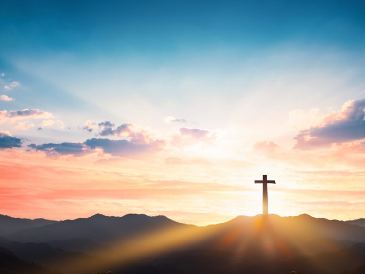 A cross stands in front of behind a beautiful sunset