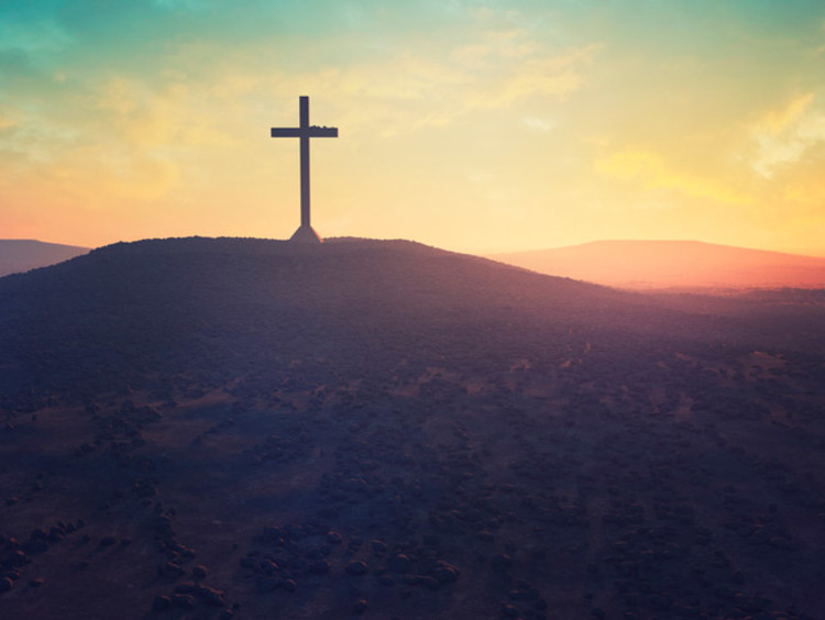 Cross on a hill in front of a sunset