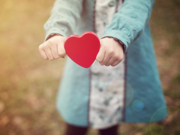Woman holds out a cutout in the shape of a red heart