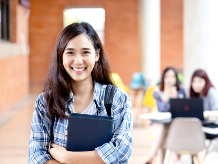 girl smiling holding school notebook