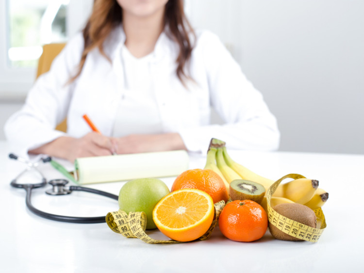 fruits and vegetables on a table and doctor sitting behind desk