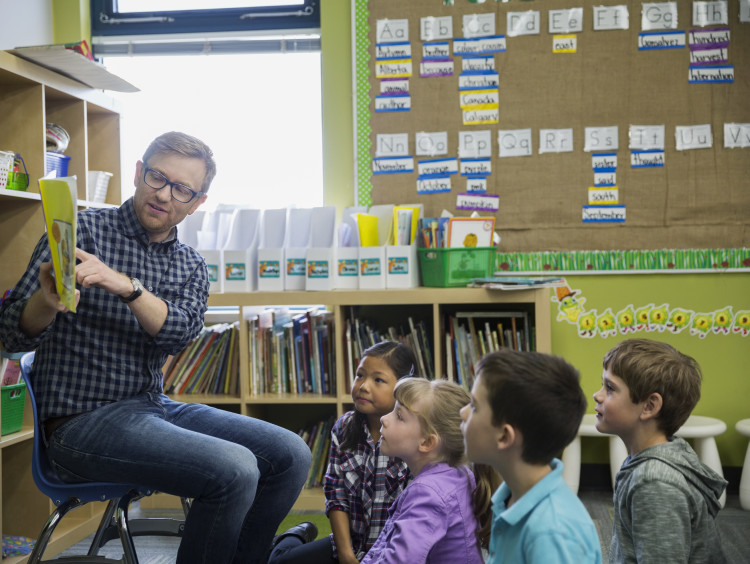 A teacher reading to his classroom