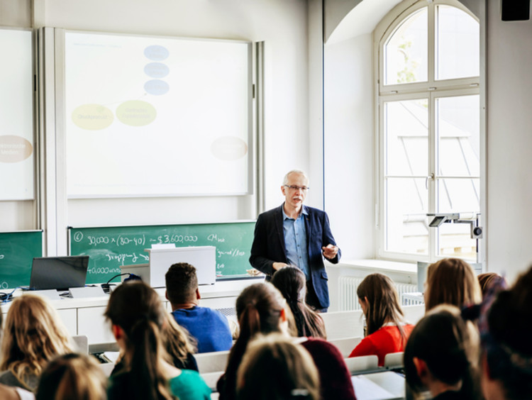 Professor teaching students at front of lecture hall