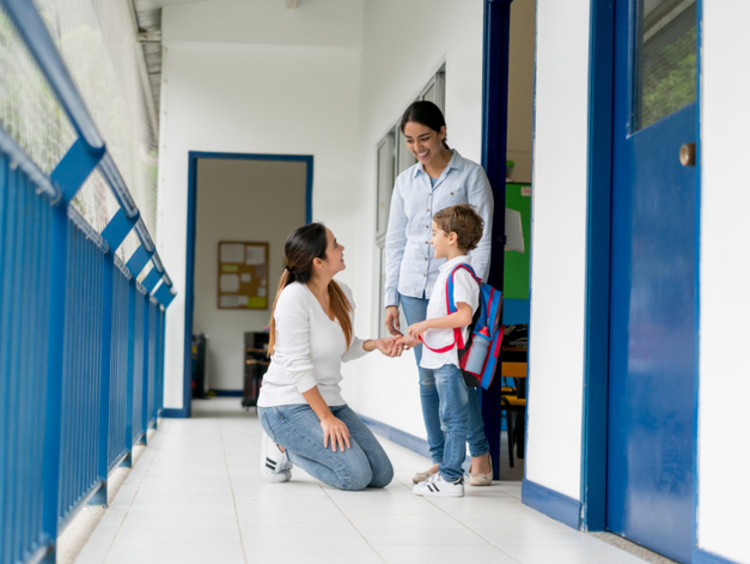 teacher talking with a student and his mother at school
