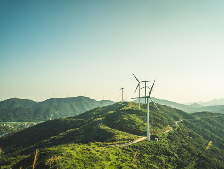 Wind mills on mountain range with overcast sky