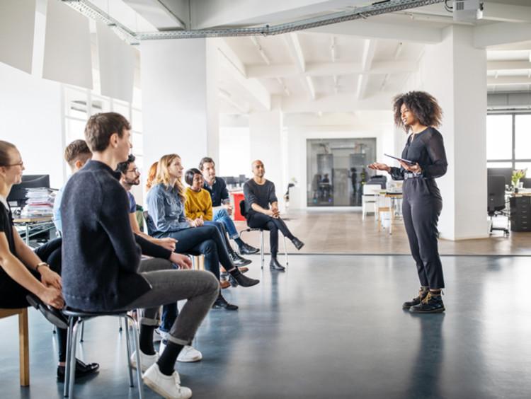 Woman speaker addressing audience in open office
