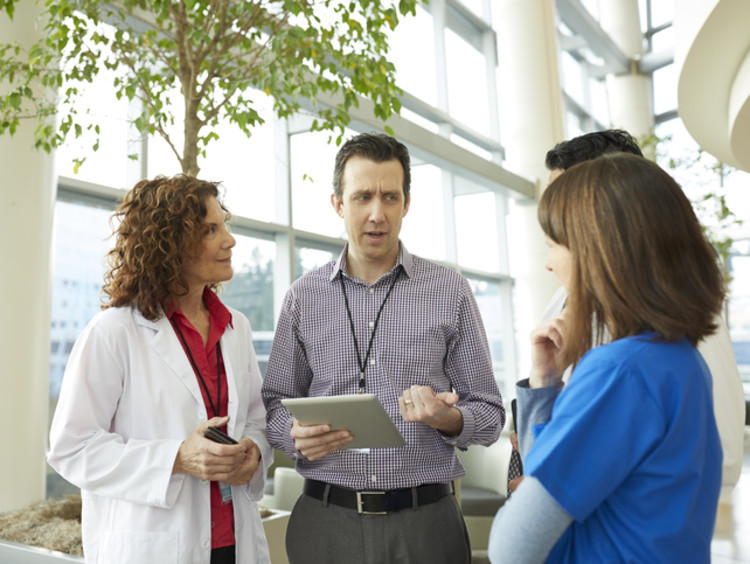 male health care administrator speaking with employees